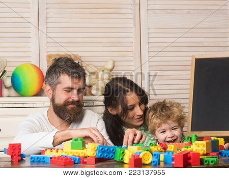 Parents And Kid With Happy Faces Make Brick Constructions.