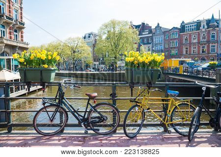 Amsterdam, Netherlands - April 20, 2017: Beautiful view of Amsterdam canals with bridge and bikes. Amsterdam, Netherlands