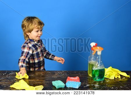 Kid with smile cleaning table with yellow rag. Boy in checkered shirt on blue background. Cleaning activities concept. Child near wooden table with cleaning supplies on.