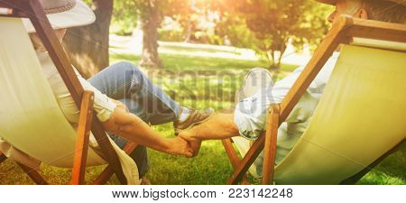 Rear view of a relaxed mature couple sitting in deck chairs at the park