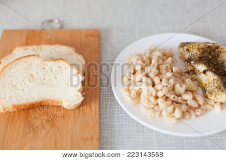 student lunch. pasta with baked fish and bread