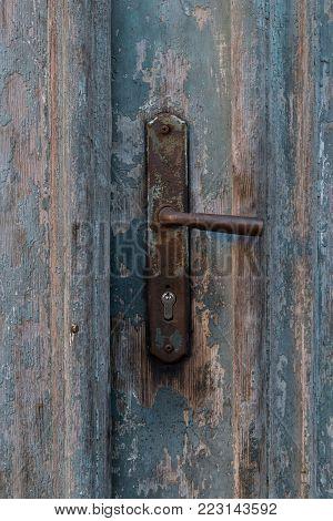 Old vintage metal door handle on old blue wooden doors. Rusty door handle