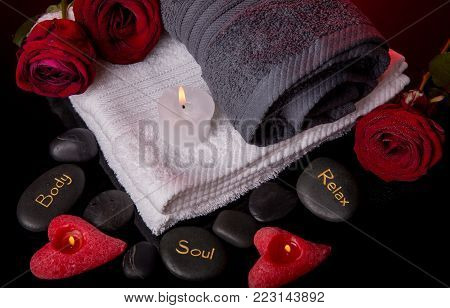 Spa concept in Valentine's Day, red roses, candles in the shape of heart, spa stones with the inscription soul, body, relax