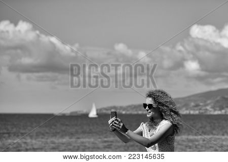Woman young beautiful with blond long curly hair taking selfie self-portrait photograph on smart phone on summer sunny day at blue sea side on blurred seascape background, horizontal picture