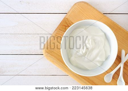Greek Yogurt In A White Bowl, Above View On A Natural Wood Cutting Board Against White Wood.