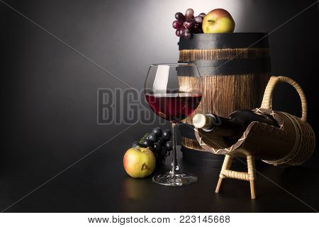 Red wine glass with bottle in sraw prop and old wooden barrel surrounded by fruits: vine and apples on black background