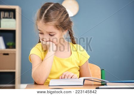 Tired little girl with textbook in classroom