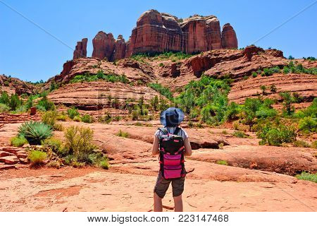 A young female Hiker trying to decide if hiking to the summit of Cathedral Rock is within her abilities given she arrived during the hottest time of day. Cathedral Rock in located in Sedona Arizona. Girl's face is not visible, no release is necessary.