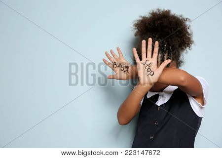 "Little African-American girl with phrase ""Stop bullying"" on light background poster"