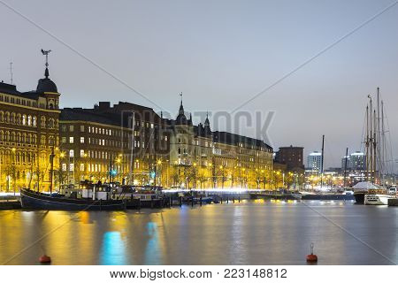 Travel Destinations. Line of Traditional Finnish Houses in Helsinki in Front of Waterline of Old Quay, Shot During Blue Hour. Horizontal Image