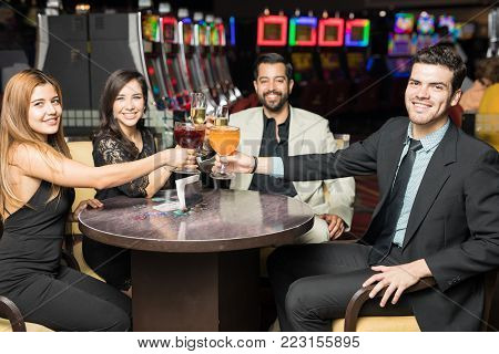 Group of lucky friends making a toast after winning some money in a casino