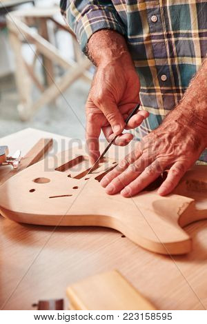 Guitar maker builds handmade wood guitar at work