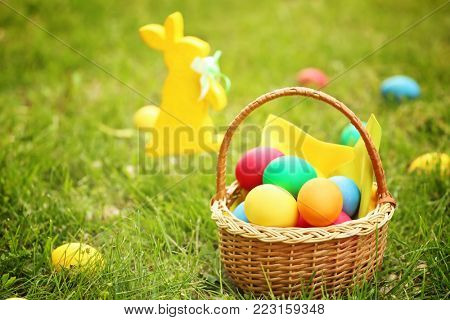 Colorful eggs in wicker basket on green grass. Easter hunt concept
