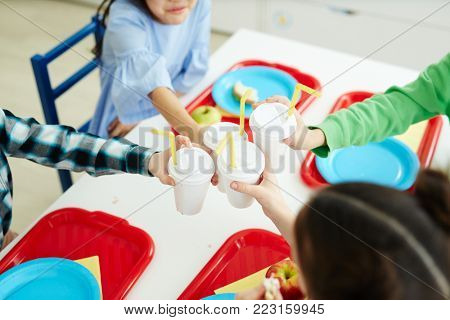 Group of classmates toasting with plastic glasses of drinks over table during lunch