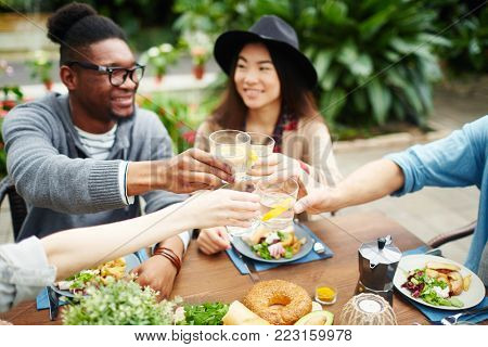 Intercultural friends toasting with glasses of homemade lemonade over dinner table served with fresh and healthy food