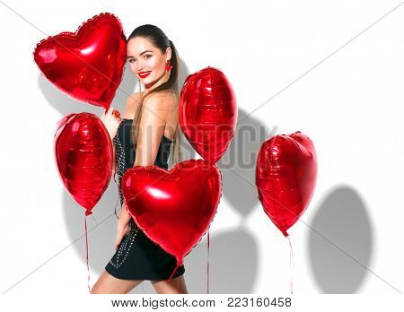 Valentine Beauty girl with red air balloons laughing, isolated on background. Beautiful Happy Young woman. Holiday party. Joyful model having fun, playing and celebrating with red color balloon
