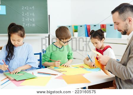 Three schoolkids and their teacher making creative toys from colorful paper at lesson