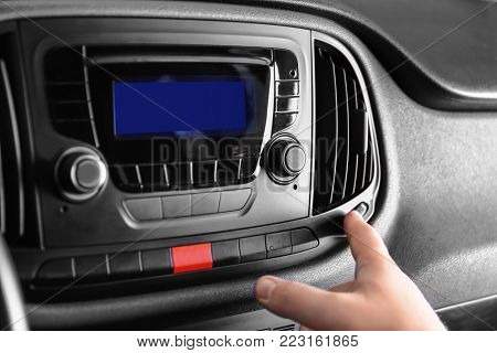 Man switching on air conditioner in car