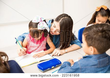 Pretty young preschool teacher tutoring one of her pupils on a writing assignment in the classroom