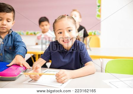 Portrait of a cute Hispanic little girl attending preschool and smiling with a toothless grin poster