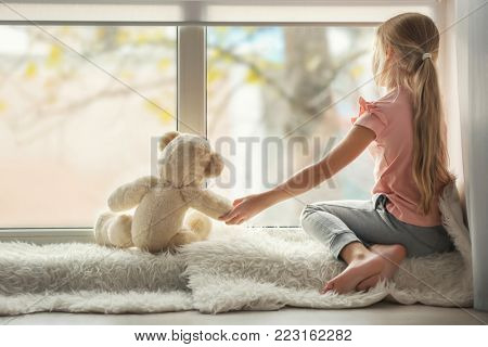 Little girl with teddy bear sitting on window sill. Autism concept poster