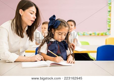Preschool teacher sitting next to one of her students and helping her with her writing assignment