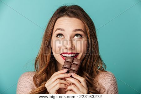 Portrait of a delighted brown haired woman with bright makeup eating chocolate bar isolated over blue background