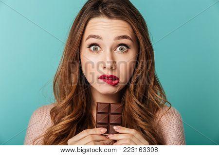 Portrait of a confused brown haired woman with bright makeup eating chocolate bar isolated over blue background