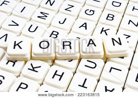 Koran text word crossword title caption label cover background. Alphabet letter toy blocks. White alphabetical letters. Koran.