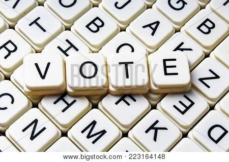 Vote text word crossword title caption label cover background. Alphabet letter toy blocks. White alphabetical letters. Vote.