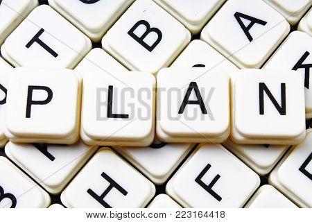 Plan text word crossword title caption label cover background. Alphabet letter toy blocks. White alphabetical letters. Plan.