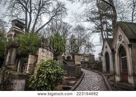 PARIS, FRANCE - DECEMBER 22, 2017: Graves from the 19th century in Pere Lachaise Cemetery in Paris, France, during a cold cloudy winter afternoon. Pere Lachaise Cemetery is the largest cemetery in Paris, hosting major french celebrities