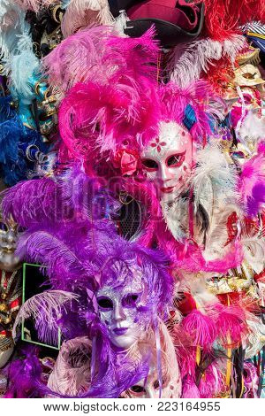 Ornated carnival masks among colorful feathers in Venice, Italy.