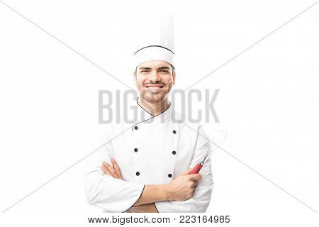 Good looking Hispanic male chef working in a bakery and holding a whisker