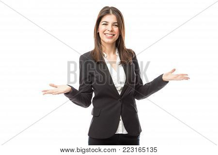 Cute young female hostess wearing a suit and opening her arms while welcoming people