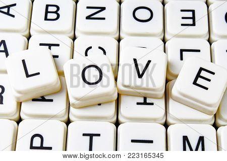 Love text word crossword title caption label cover background. Alphabet letter toy blocks. White alphabetical letters. Love.