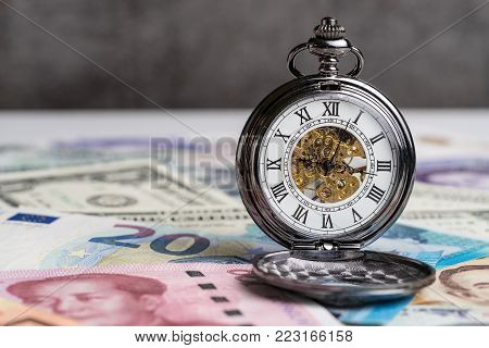 Time for money, counting down for world financial crisis concept, mechanical vintage pocket watch on international major countries banknotes.
