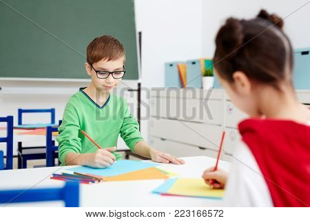 Little secontary schoolkids with crayons drawing on papers in classroom