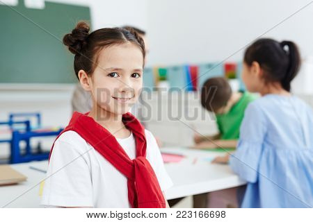 Cute schoolgirl looking at camera during break between lessons with classmates on background