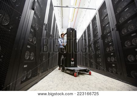 Technical manager or IT-support staff with loadlifter pushing it while walking along aisle between storage hardware