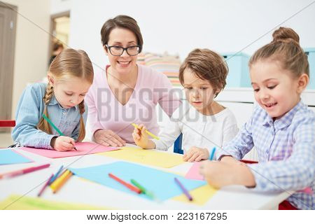 Happy teacher and three kids sitting by table at drawing lesson in kindergarten
