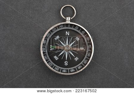 Plastic touristic compass on black cardboard background