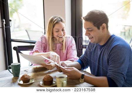 Portrait of a happy young couple reading menu card and deciding what to order while hanging out in a restaurant