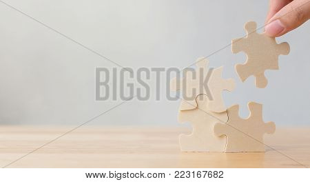 Hand of male or female putting jigsaw puzzle connecting on wooden desk and wall background, Strategic management and business solutions for success