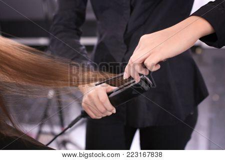 Professional stylist straightening woman's hair in salon, closeup