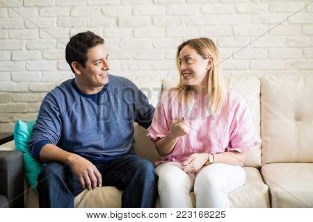 Happy hispanic woman telling her husband about her pregnancy test result while sitting on sofa at home