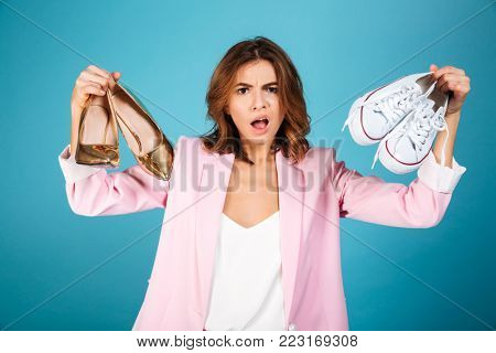 Portrait of a confused woman dressed in pink suit holding pair of high heels shoes and pair of sneakers isolated over blue background