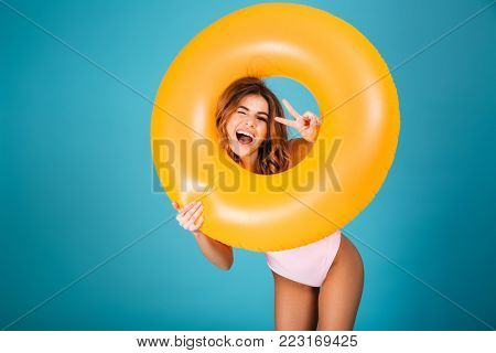 Portrait of a cheerful girl dressed in swimsuit looking through inflatable ring and showing peace gesture isolated over blue background