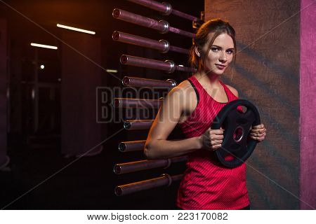 Girl athlete keeps the disc from the bar weighting agent for doing crossfit and fitness. Concept of sports equipment and weight loss.