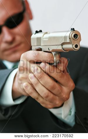 Security personnel in a suit armed with a pistol
